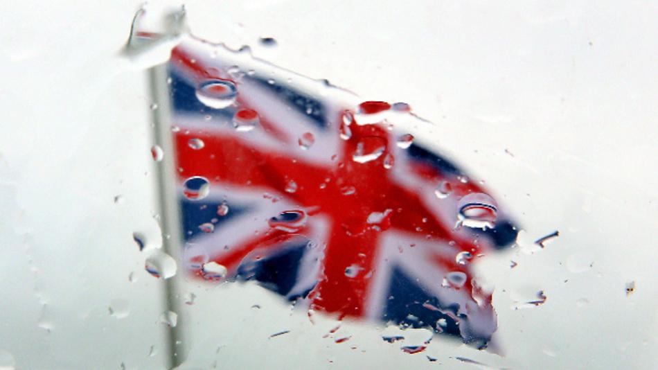Blick durch eine vom Regen benetzte Autoscheibe auf eine britische Fahne.