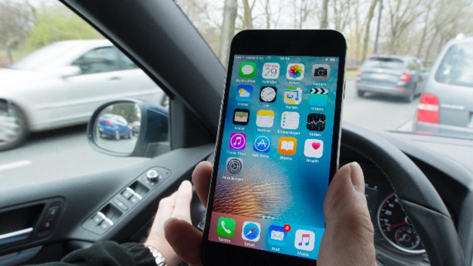 Eine Hand am Smartphone, die andere am Lenkrad des Fahrzeugs (gestelltes Foto).