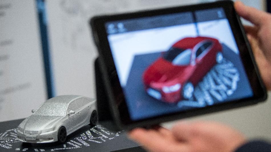 Automodell, das durch den Einsatz von Augmented Reality auf dem Tablet in roter Farbe zu sehen ist.