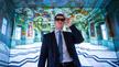"""Markus Söder (CSU), Bayerischer Ministerpräsident, trägt während seines Besuchs im Rechenzentrum vom Supercomputer """"SuperMUC-NG"""" eine 3D Brille mit Bewegungssensoren und steht in einer Simuation vom Kaisersaal Bamberg."""