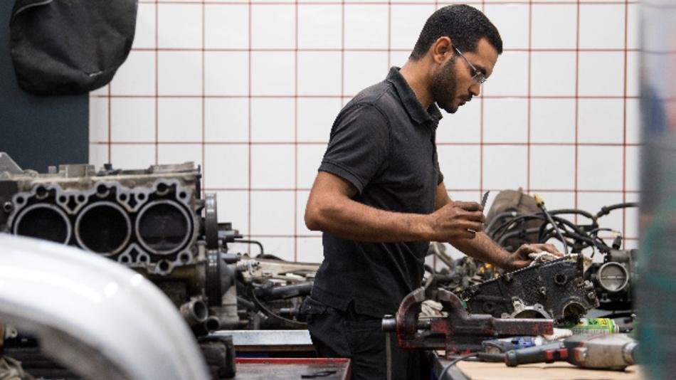 Ein Mechatronik-Auszubildender arbeitet am Austausch-Motor eines Porsche.