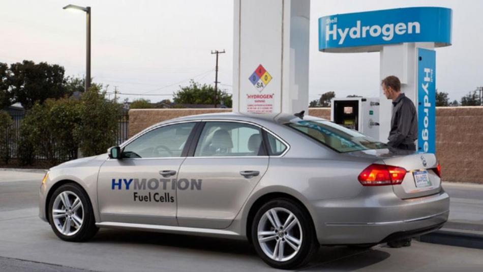 Fahrzeug von Volkswagen mit der Aufschrift »HYMOTION Fuel Cells« an einer Wasserstofftankstelle.
