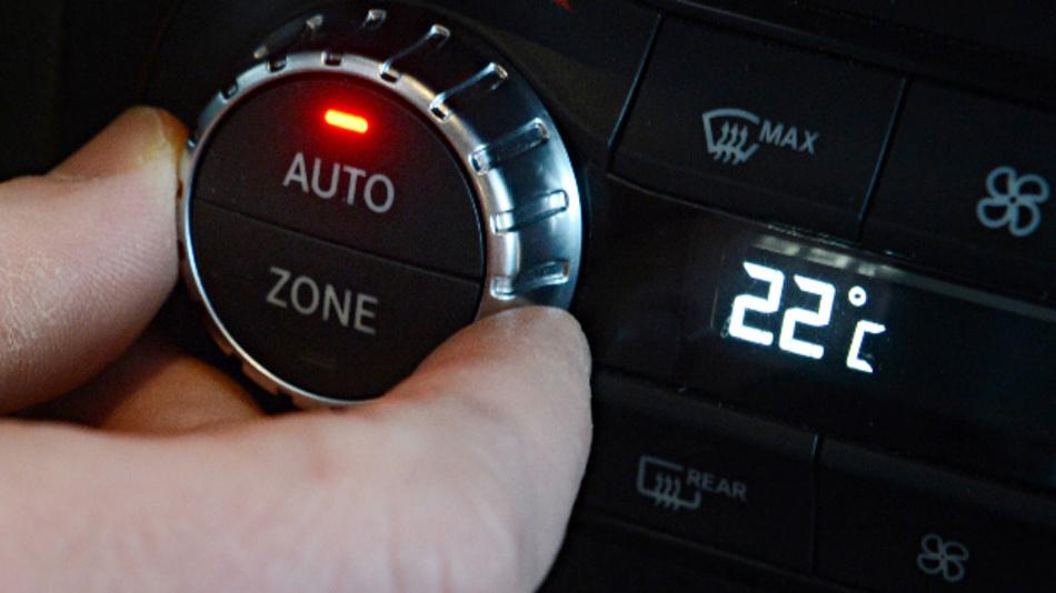 Ein Mann stellt die Temperatur am Bedienelement der Klimaanlage ein.