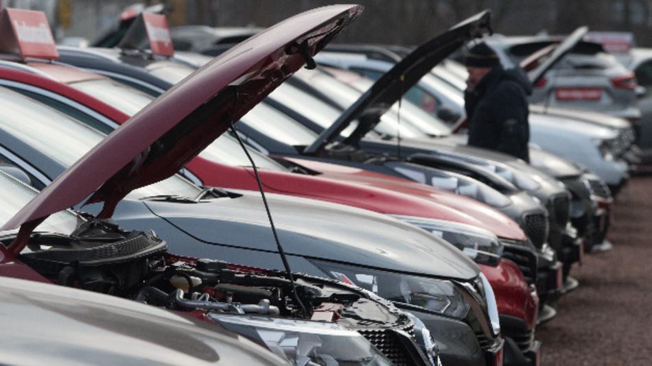 Neu- und Gebrauchtwagen stehen bei einem Autohändler nebeneinander.
