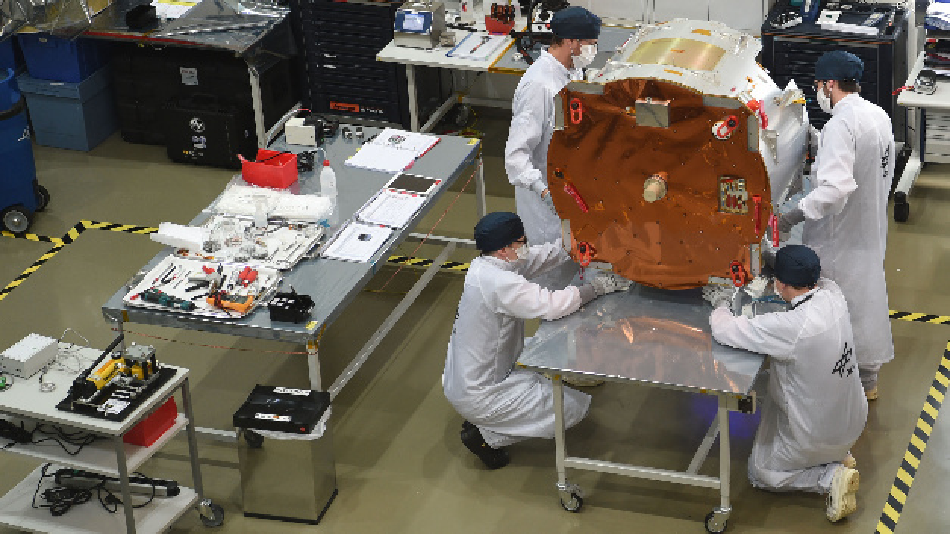 Ingenieure arbeiten am Deutschen Zentrum für Luft-und Raumfahrt (DLR) an einem Forschungssatelliten, der als fliegendes Gewächshaus um die Erde kreist. Dort sollen Tomaten zum Keimen gebracht werden.