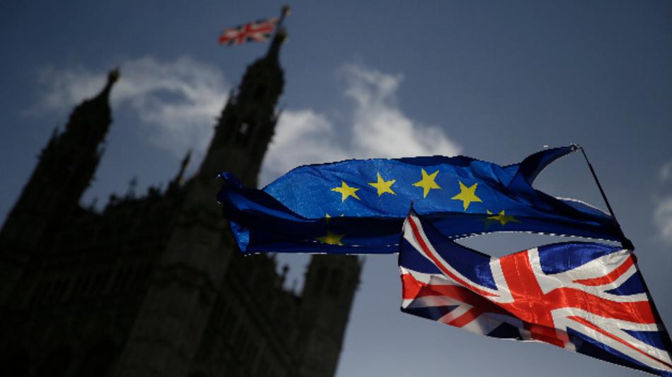 Eine EU-Flagge und eine britische Nationalflagge wehen vor dem britischen Parlament im Palace of Westminster, während einer Demonstration gegen den Brexit.
