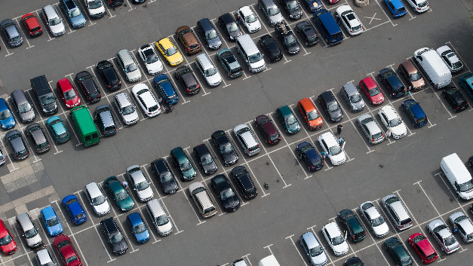 Zahlreiche Autos stehen auf einem Parkplatz.