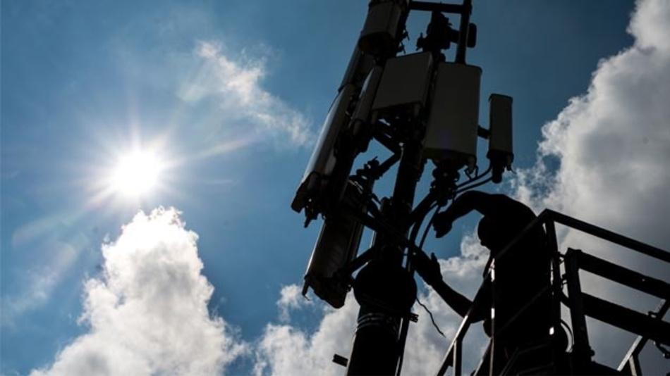 Ein Servicetechniker arbeitet an einem Mobilfunkmast.