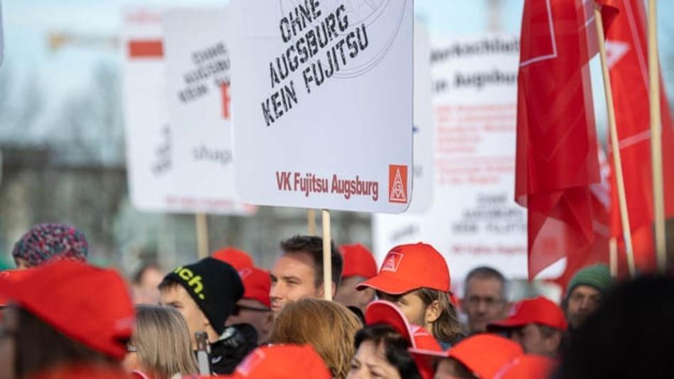Teilnehmer einer Kundgebung der IG Metall gegen die Schließung des Fujitsu-Werkes Augsburg stehen auf dem Willy-Brandt-Platz an der Messe und »begrüßen« Kunden und Management zur Hausmesse »Fujitsu Forum«.