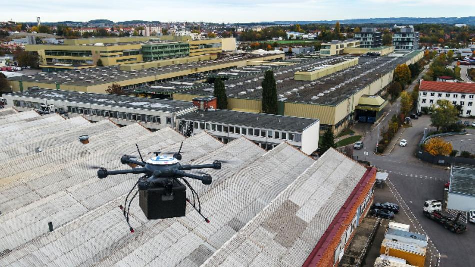 Eine automatisierte Lieferdrohne über den Dächern der Werkshallen des ZF-Werks 2 in Friedrichshafen. Sie bringt ein dringend benötigtes Ersatzteil auf dem Luftweg in die Instandhaltungswerkstatt.