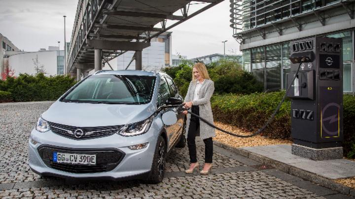 Frau steckt Ladekabel einer Opel Ladesäule an den Opel AmperaE an.