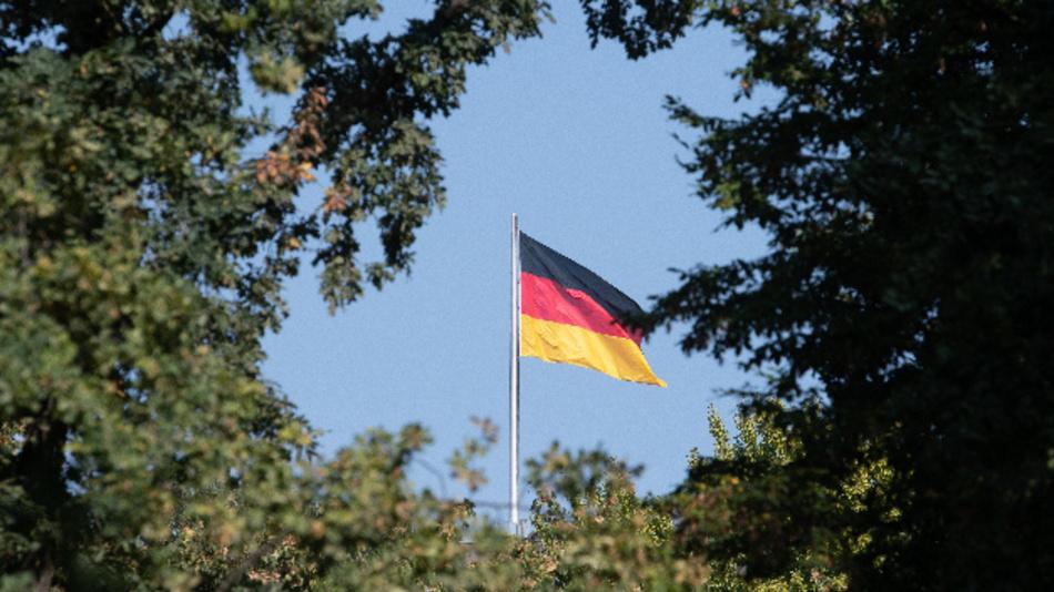 Eine Deutschlandfahne weht zwischen Bäumen im Wind.