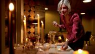 Frau zündet kerzen an einem festlich beleuchteten Esstisch an.