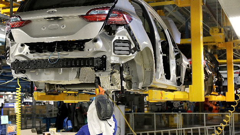 Ein Ford Mitarbeiter arbeitet in der Produktion an einer Karosserie.