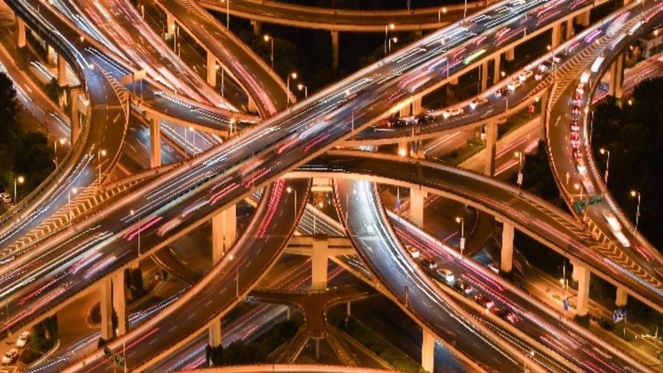 Das Bild zeigt den Blick auf ein Autobahnkreuz in Shanhgai bei Nacht. Der für deutsche Autobauer wichtige chinesische Automarkt steuert für das Gesamtjahr 2018 auf den ersten Absatzrückgang seit mindestens zwei Jahrzehnten zu.