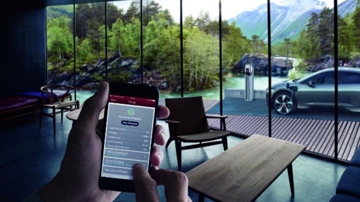 Mann steuert per Smartphone den Ladevorgang des Jaguar I-Pace, der im Hintergrund an einer Ladesäule angeschlossen ist