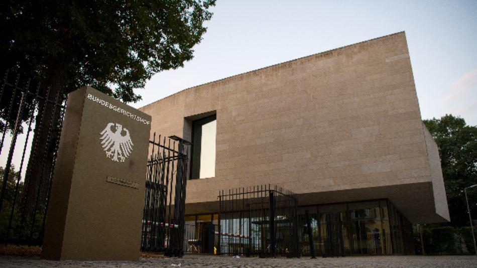 Eine Außenaufnahme des Bundesgerichtshofs (BGH) mit dem Hinweisschild zum Bundesgerichtshof, auf dem der Bundesadler abgebildet ist.