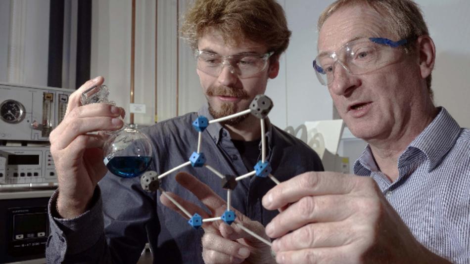 Doktorand Benjamin Kintzel (l.) und Prof. Dr. Winfried Plass diskutieren über ein von ihnen entwickeltes Molekül, das möglicherweise in einem Quantencomputer Verwendung finden kann.