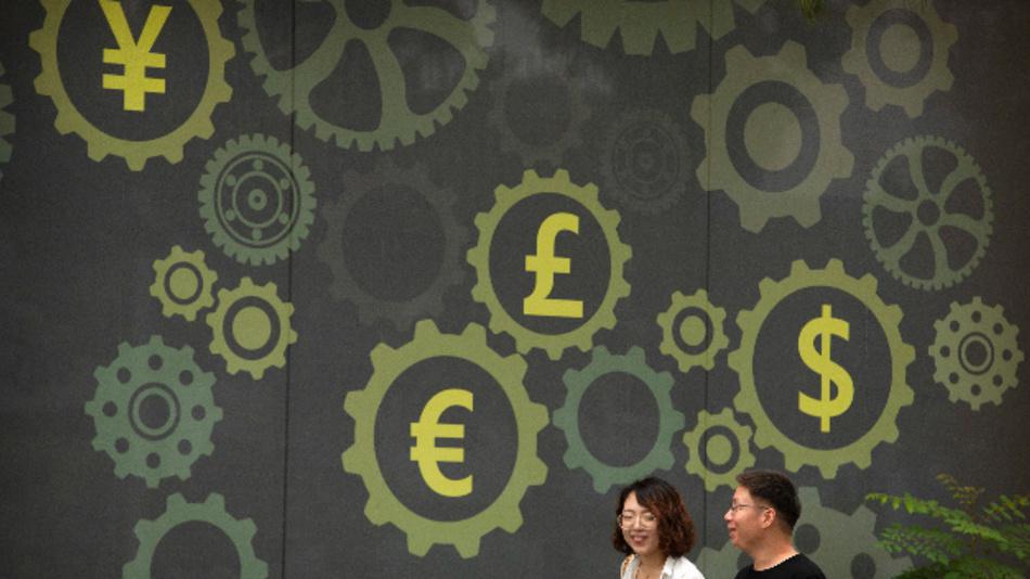 Menschen gehen in Peking an einer Wand vorbei, welche die Symbole für den Yen, Euro, Dollar und britischen Pound zeigt.