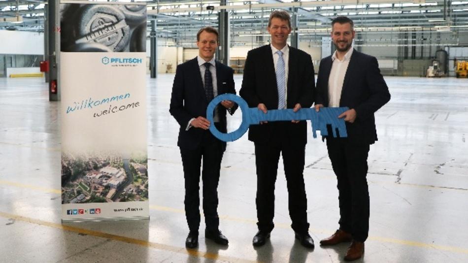In dieser Halle wird Pflitsch das neue Kompetenzzentrum Kabelkanäle realisieren: Die beiden geschäftsführenden Gesellschafter Mathias Stendtke (l.) und Roland Lenzing (r.) bei der Schlüsselübergabe mit Thomas Velten (Magna Powertrain)