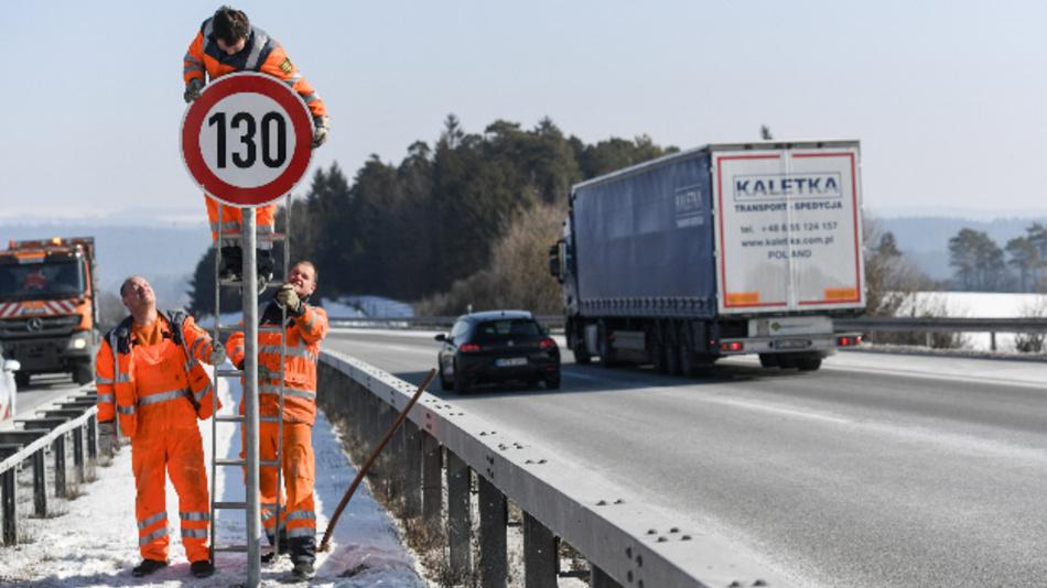 Straßenwärter montieren an der Autobahn A81 am Hegaublick ein Schild mit der Aufschrift »130«.