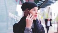Frau telefoniert vor einem Geschäft mit ihrem Smartphone.