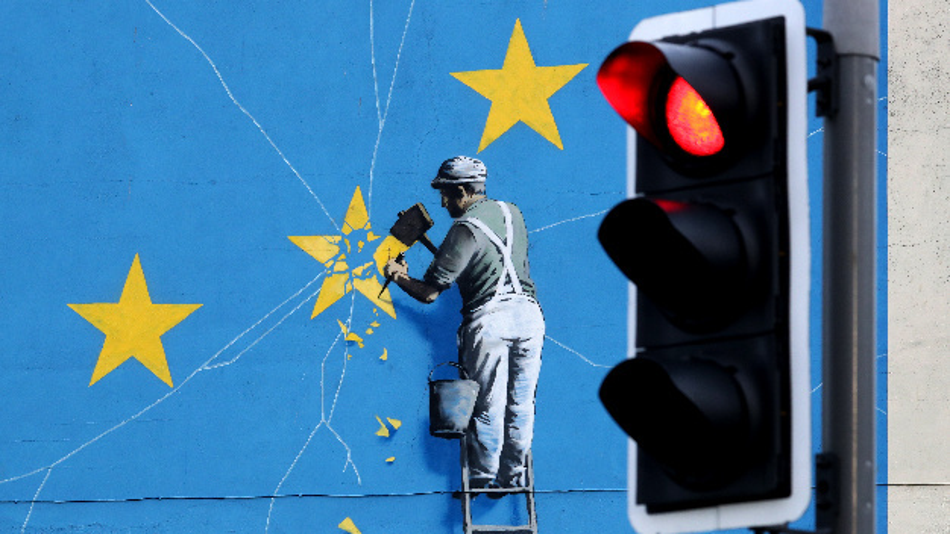 Das Brexit-Wandbild von Banksy zeigt einen Mann, der mit einem Hammer einen Stern aus der EU-Flagge entfernt – im Vordergrund ist eine rote Ampel.