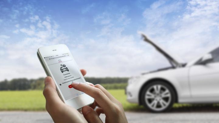 Webseite auf Smartphone und Pannenfahrzeug im Hintergrund