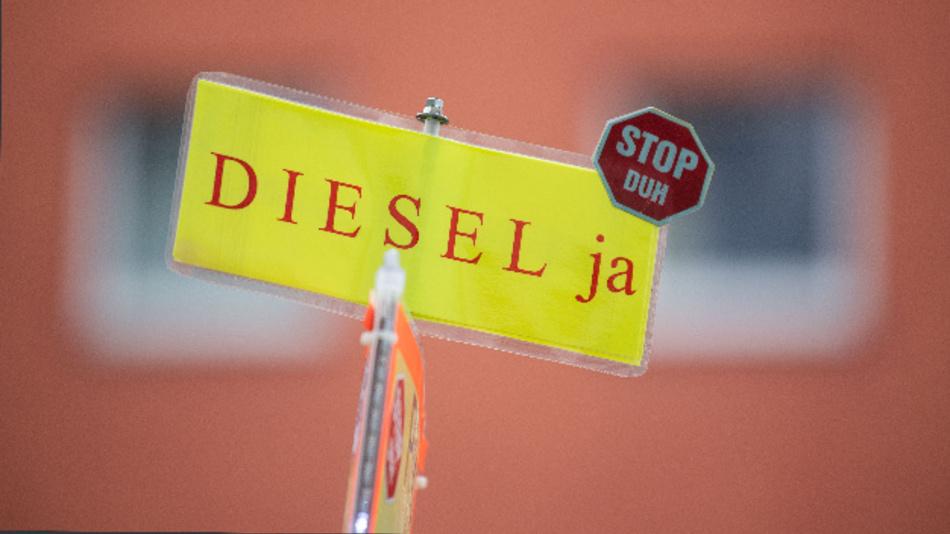 Ein Gegner der Diesel-Fahrverbote hält während einer Demonstration am Neckartor ein Plakat mit der Aufschrift »Diesel ja – Stop DUH«.