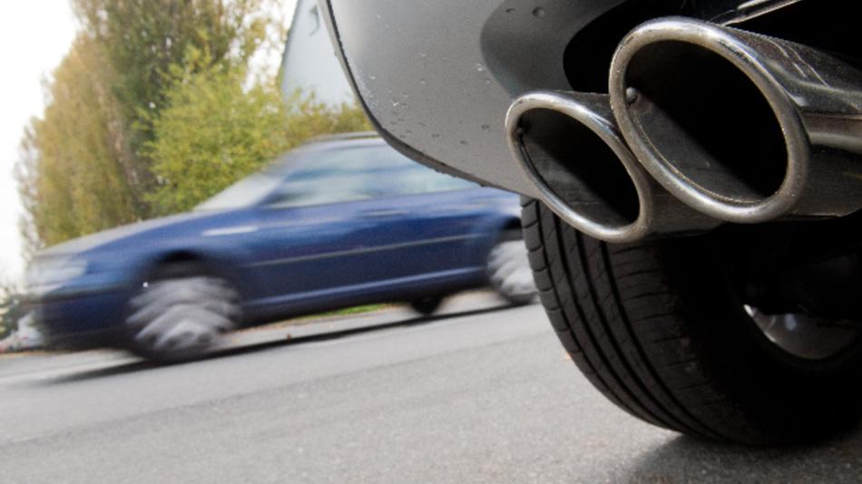 Die Abgasanlage eines Autos mit Dieselmotor an einer Straße.