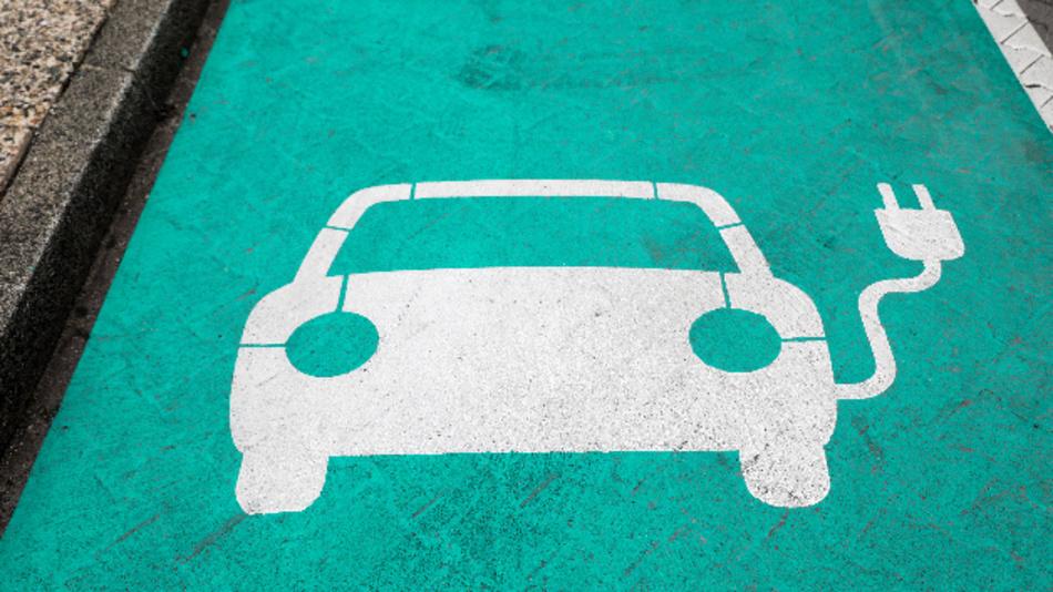 Ein Piktogramm eines Autos auf einem grünen Grund markiert einen Parkplatz mit Ladesäule für Elektrofahrzeuge.