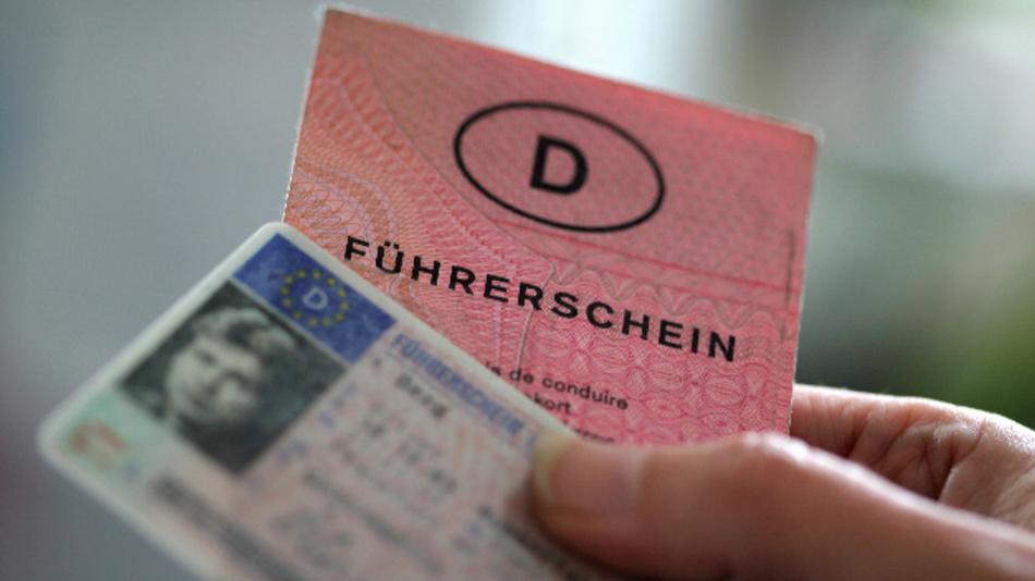 Zwei Führerscheine verschiedener Generationen hält eine Frau in der Hand. In Deutschland stecken unterschiedliche Führerscheintypen in Portemonnaies und Handschuhfächern. Bis 2033 müssen nach einer EU-Vorgabe Millionen von Dokumenten ausgetauscht werden – aber wie genau soll das über die Bühne gehen?