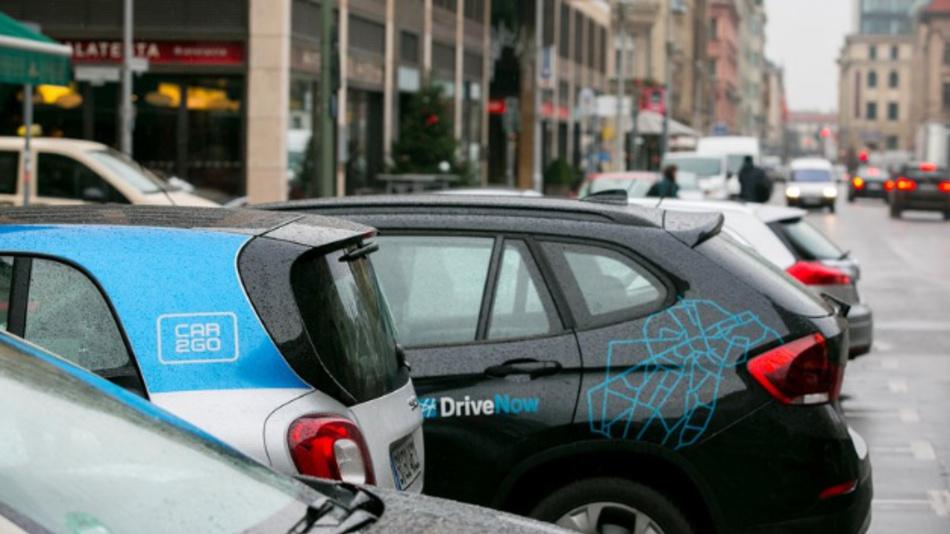 Geparkte Carsharing-Fahrzeuge von car2go und DriveNow stehen nebeneinander.