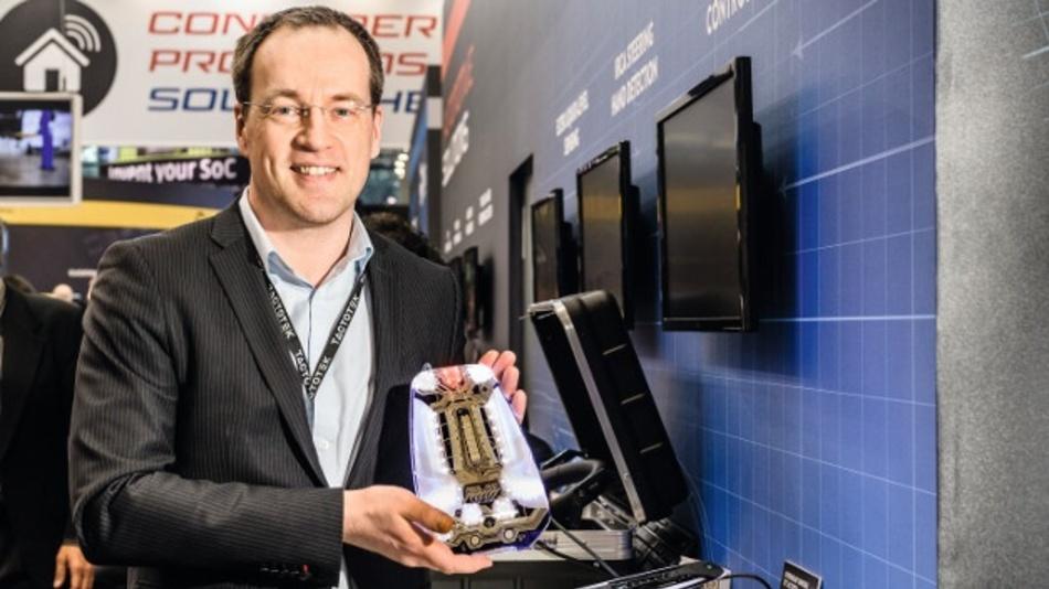 """Perttu Korhonen zeigt am Tactotek-Stand ein gebogenes Teil für die Mittelkonsole eines Fahrzeugs. Die """"elektronische Schicht"""", die Leiterbahnen, Sensoren und LEDs enthält, ist nur 3 mm dick."""