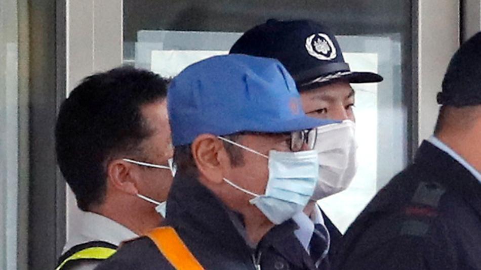 Ein maskierter Mann mit blauer Mütze, von dem man annimmt, dass es sich um den ehemaligen Nissan-Vorsitzenden Ghosn handelt, verlässt mit Sicherheitskräften das Tokyo Detention Center.