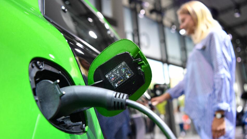 Eine Frau steht hinter einem Ladestecker an einem Smart Electric Drive.