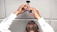 Mann installiert einen Bewegungsmelder an einer Zimmerdecke.