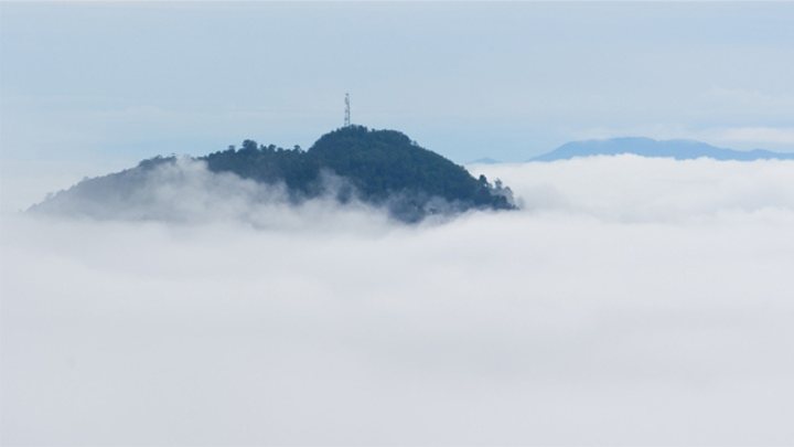 Sendemast am Horizont auf Berggipfel über den Wolken.