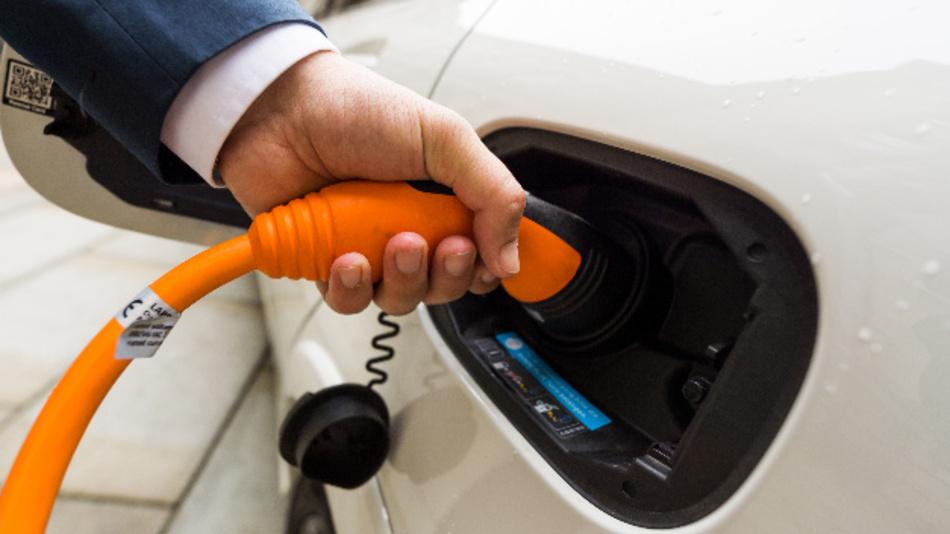 Ein Mann hält einen Stecker in die Ladesteckdose eines Mercedes-Benz B-Klasse Electric Drive.