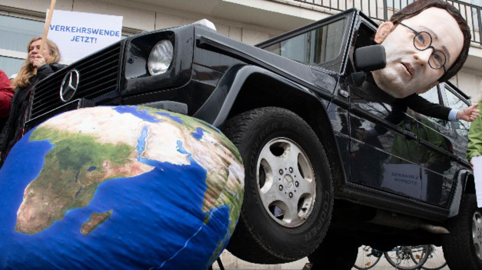 Ein Mann mit einem Pappkopf, der Bundesverkehrsminister Scheuer (CSU) darstellen soll, sitzt bei einer Protestaktion vor dem Bildungswerk der Wirtschaft in einem SUV, das symbolisch über die Erde fährt.