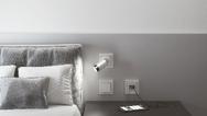 Plug-and-light-Strahler ist als Leseleuchte auf ein Bett gerichtet