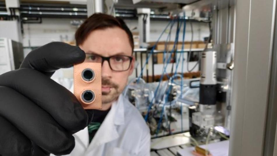 Johannes Rudolph prüft einen im 3D-Multimaterialdruck gefertigten Wärmetauscher