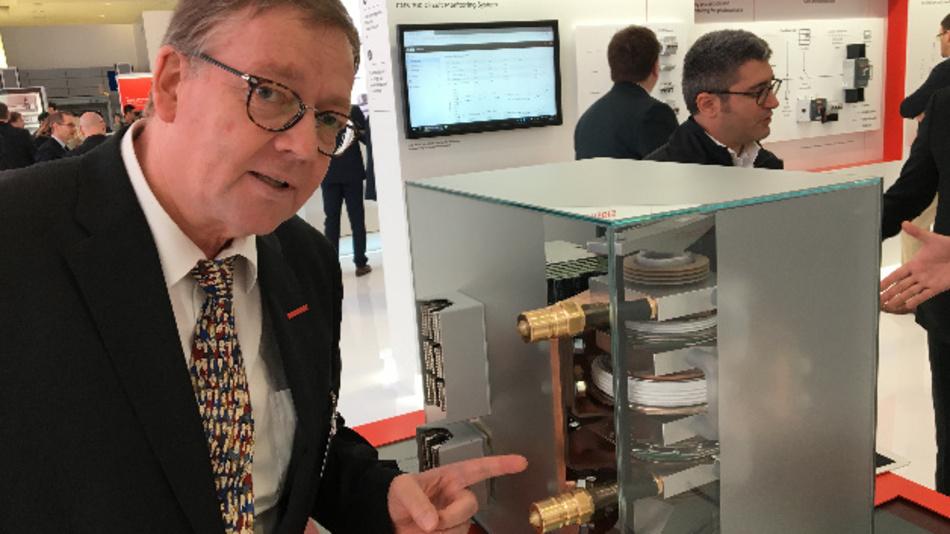 Reiner Schönrock, Vice President Head of Strategic Product and Innovation Communications von ABB, vor dem neuen digitalen Circuit Breaker. Nach seinen Worten wird er die Netztechnik ähnlich einschneidend verändern wie der Übergang von Vakuumröhren zu Transistoren. Im Vordergrund sind die Anschlüsse für die Wasserkühlung zu sehen.