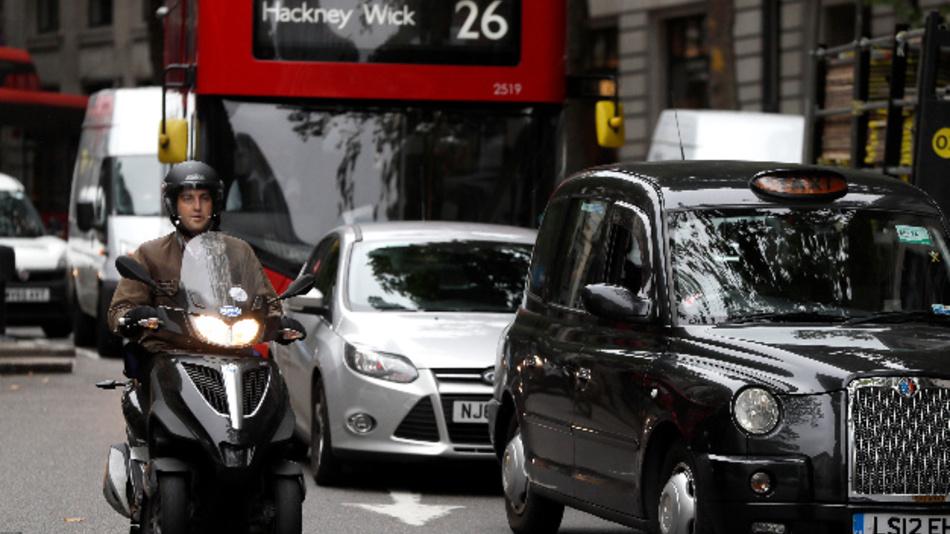 Autos, Busse und Motorroller fahren auf einer Straße in der Londoner Innenstadt.