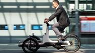 Ein Mann fährt auf einem Prototypen eines Elektro-Lastenrades von Volkswagen.