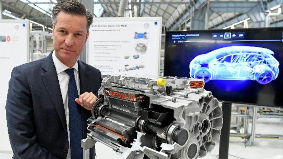 Thomas Schmall, Vorstandsvorsitzender der Volkswagen Konzern Komponente, steht neben dem Modell des E-Antriebs APP310-2.0 in einer Fertigungshalle im VW-Werk Salzgitter.