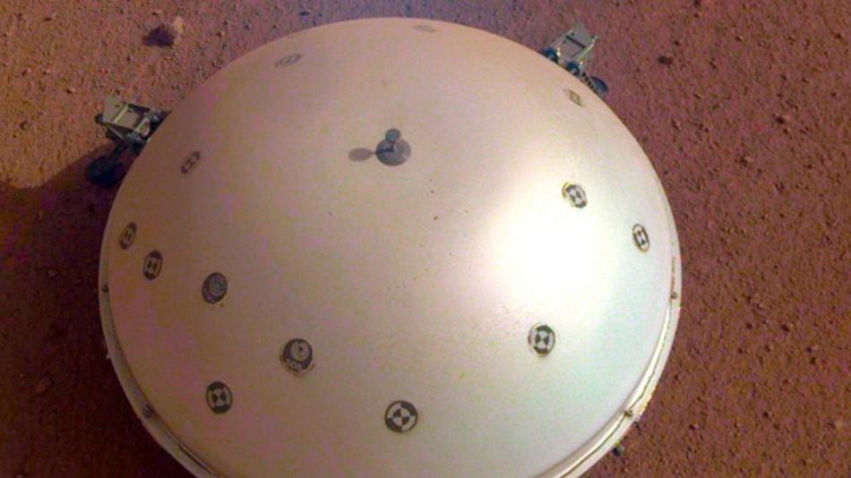 Dieses Bild, das am 19. März 2019 von einer Kamera auf der Mars InSight-Sonde der NASA aufgenommen wurde, zeigt den gewölbten Wind- und Wärmeschild des Rovers, der sein Seismometer, das seismische Experiment für die Innenstruktur und die Marsoberfläche im Hintergrund bedeckt.