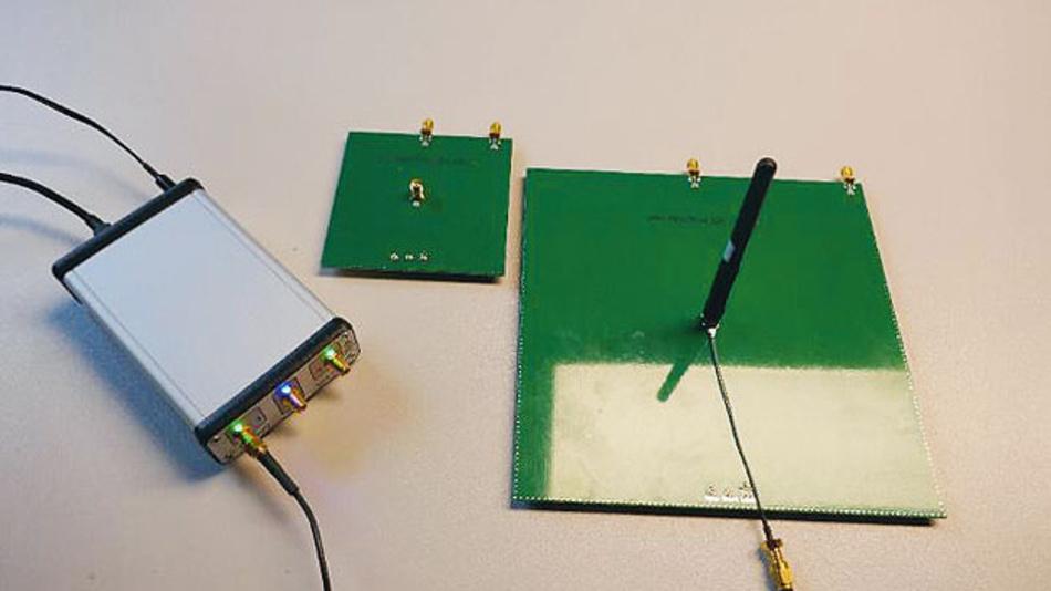 Bild 3. Für die Antennenmessungen dient der Vektor-NetzwerkAnalysator (VNA) von MegiQ (links), und zwei Testplatinen mit 95 mm × 95 mm Massefläche (Mitte) und 190 mm × 190 mm Massefläche (rechts). Die Antenne wird zur Messung vertikal auf der Testplatine montiert.
