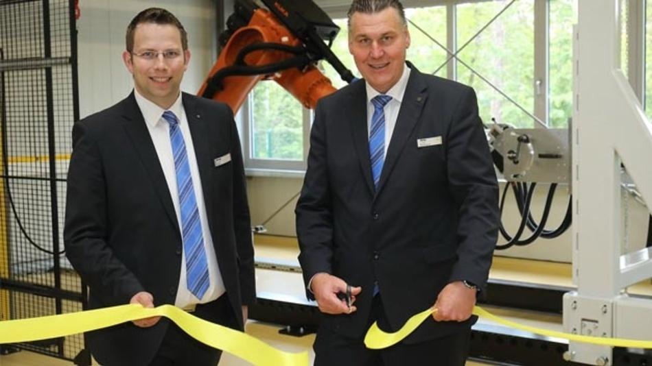 Christian Schumacher (rechts), Geschäftsführer von Harting Customised Solutions und Matthias Wiehe, Head of Global Project Engineering, eröffnen den Prüfstand für Wagenübergangssysteme.