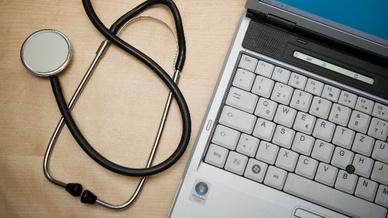 Ein Stethoskop liegt neben einem Laptop (Illustration)